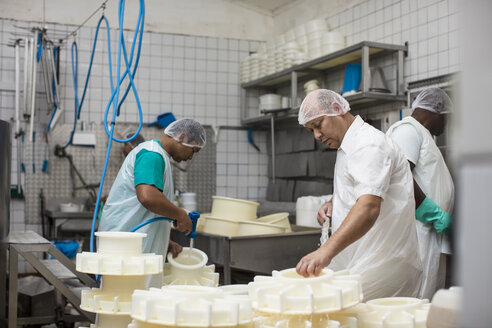 Cheese factory workers cleaning containers with hose - ZEF11019
