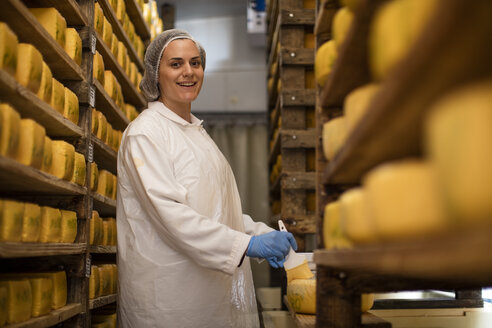 Cheese factory worker applying wax on cheese - ZEF11022