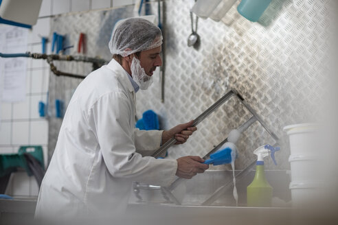 Cheese factory worker cleaning container parts - ZEF11055