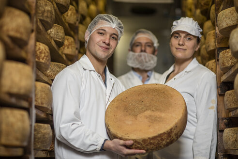 Cheese factory workers proudly holding loaf of cheese - ZEF11061