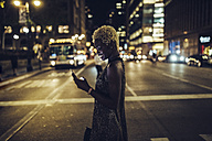 USA, New York City, smiling young woman on Times Square at night looking at cell phone - GIOF01567