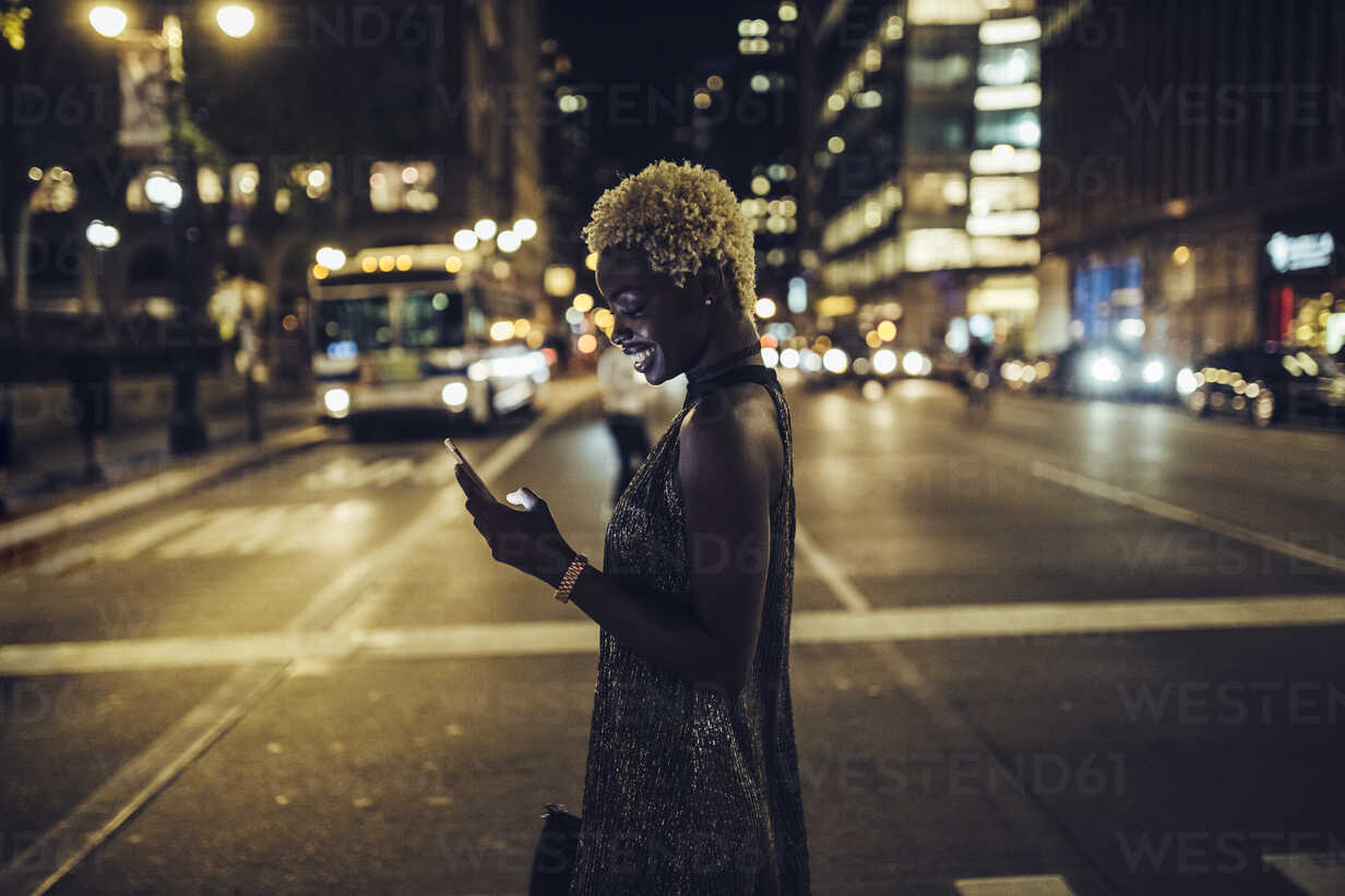 USA, New York City, smiling young woman on Times Square at night looking at cell phone - GIOF01567 - Giorgio Fochesato/Westend61