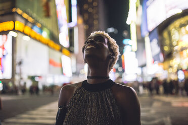 USA, New York City, smiling young woman on Times Square at night looking up - GIOF01570