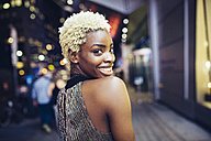 USA, New York City, smiling young woman on Times Square at night - GIOF01573