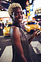 USA, New York City, portrait of smiling young woman on Times Square at night - GIOF01576
