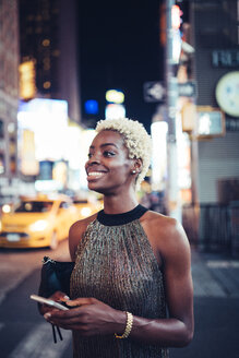 USA, New York City, smiling young woman waiting on Times Square at night - GIOF01579