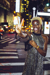 USA, New York City, young woman showing victory sign on Times Square at night - GIOF01582