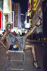 USA, New York City, happy young woman on Times Square at night - GIOF01585