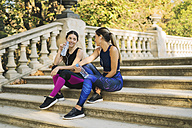 Two sportive young women sitting on stairs with bottles and earbuds - EBSF01791