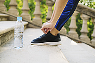 Close-up of shoe and water bottle of sportive woman - EBSF01803