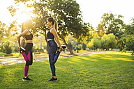 Two young women stretching in park at sunset - EBSF01824