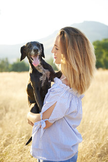Happy woman with her dog in nature - JCF00058