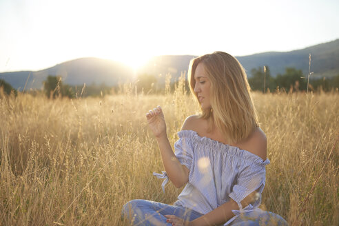 Blond woman sitting on meadow at backlight - JCF00061