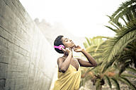 Spain, woman with eyes closed listening music with pink headphones - SIPF00972