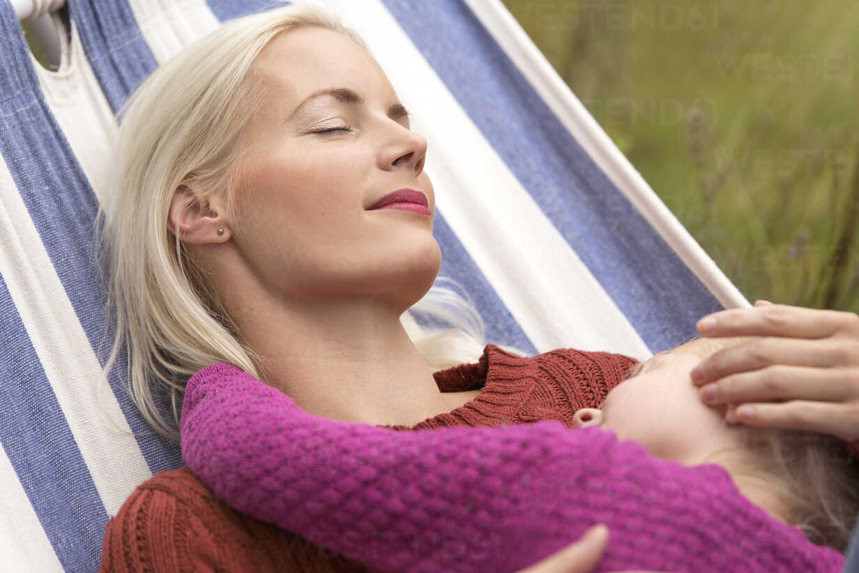 Mother and little daughter relaxing together in a hammock - MIDF00796 - Miriam Dörr/Westend61