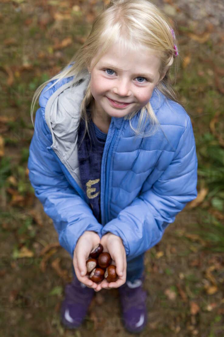 Portrait of smiling blond little girl holding chestnuts in her hands - MIDF00802 - Miriam Dörr/Westend61