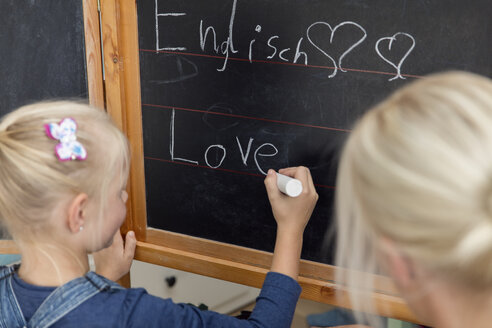Mother watching her daughter writing the word 'love' on blackboard - MIDF00805