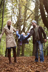Parents playing with daughter in the autumnal forest - MIDF00811