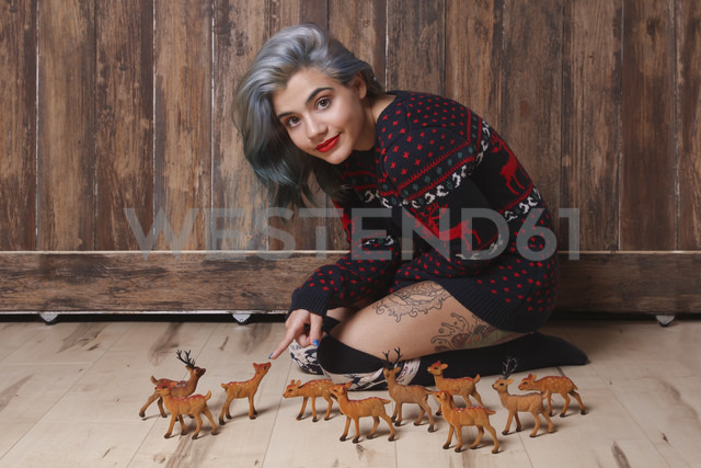 Portrait of smiling young woman wearing patterned knit pullover sitting on the floor with deer figurines - RTBF00461