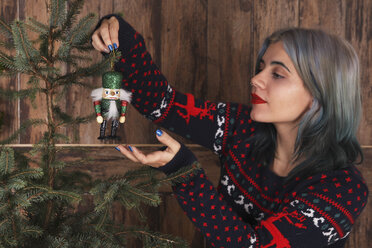 Young woman decorating Christmas tree with nutcracker figure - RTBF00464