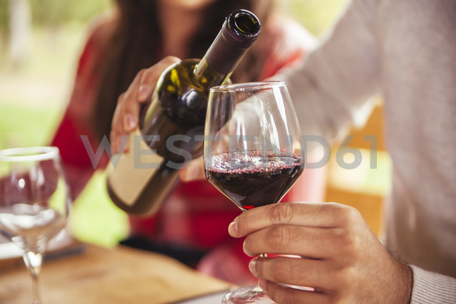 Man pouring red wine into glass - ZEDF00377