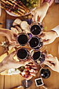 Friends clinking red wine glasses - ZEDF00383