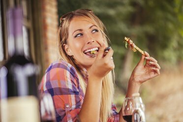 Smiling woman eating outdoors - ZEDF00389