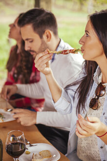 Woman with friends eating outdoors - ZEDF00401