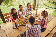 Friends socializing at outdoor table with red wine and cold snack - ZEDF00407