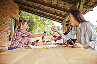 Friends clinking red wine glasses at table in vineyard - ZEDF00410