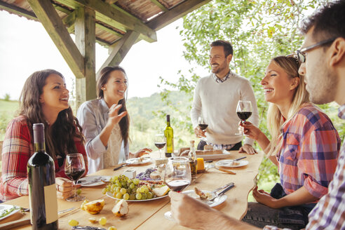 Friends socializing at outdoor table with red wine and cold snack - ZEDF00413
