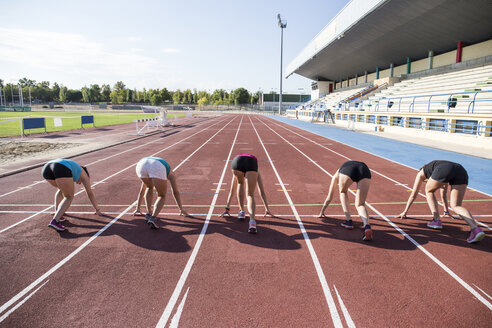 Female runners on tartan track in starting position - ABZF01377