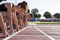 Female runners on tartan track in starting position - ABZF01380
