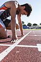 Runner on tartan track in starting position - ABZF01395