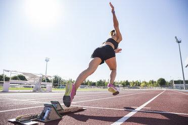 Female runner on tartan track starting - ABZF01398