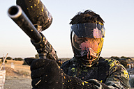 Paintball player with paintball mask and paintball gun stained with paint - ABZF01431