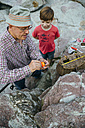 Grandfather teaching grandson fishing at rock coast - DAPF00420