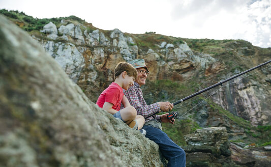 Smiling grandfather and grandson fishing together sitting on rock - DAPF00426