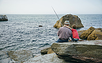 Grandfather and grandson fishing together at the sea sitting on rock - DAPF00429