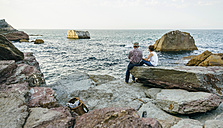 Senior couple fishing at the sea sitting on rock - DAPF00435