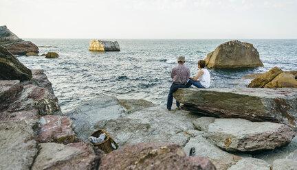 Senior couple fishing at the sea sitting on rock - DAPF00435