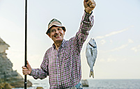 Happy senior man holding fish on fishing line - DAPF00441