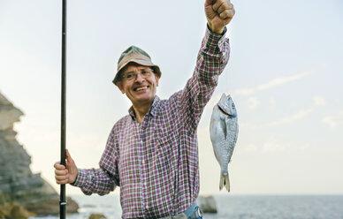 Happy senior man holding fish on fishing line - DAPF00441