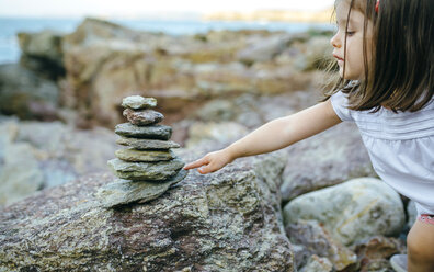 Girl with stack of stones at rocky coast - DAPF00447