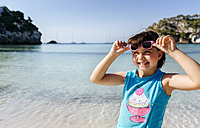 Portrait of smiling little girl standing in front of the sea - MGOF02559