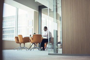 Businessman working alone in office - WESTF21816