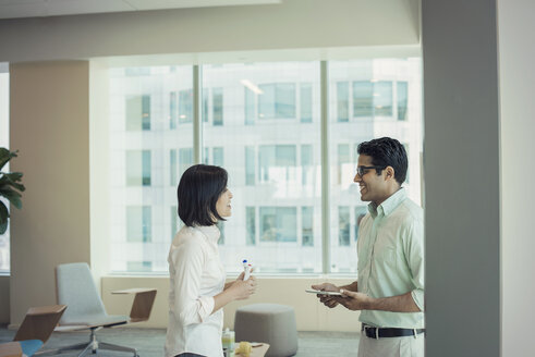 Businessman and woman talking in office - WESTF21858
