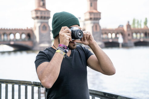 Germany, Berlin, man taking pictures with camera in front of Oberbaum Bridge - TAMF00705