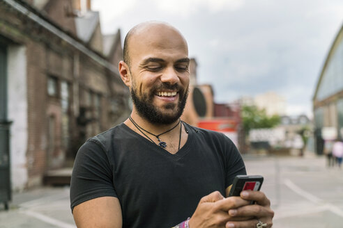 Portrait of happy man text messaging - TAMF00714