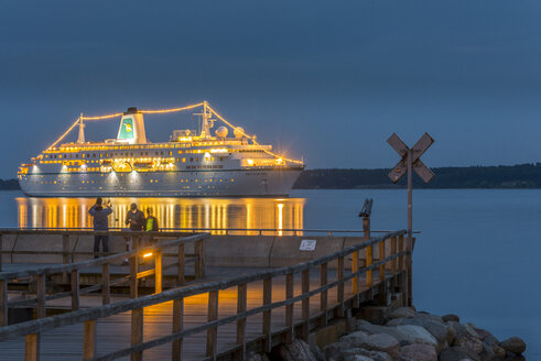 Germany, Eckernfoerde, view to lighted cruise liner and pier in the foreground - KEB00418